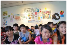 The children with their artworks in the background.
