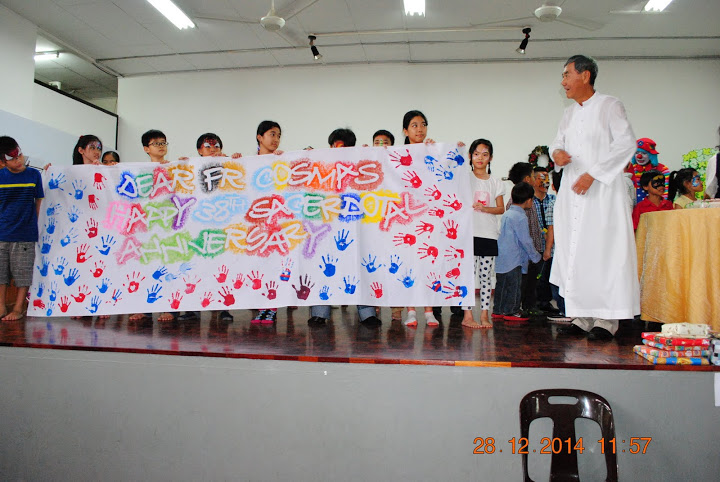Fr Cosmas (right) receiving the hand-printed message from the children during the four-in-one celebration at the St Simon Catholic Church Likas parish hall on Dec 28, last year.