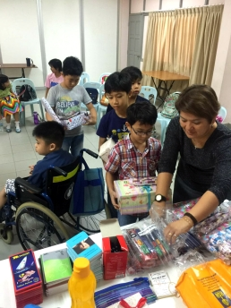 A teacher lending a hand to the students as they put finishing touches to their shoe box gifts.